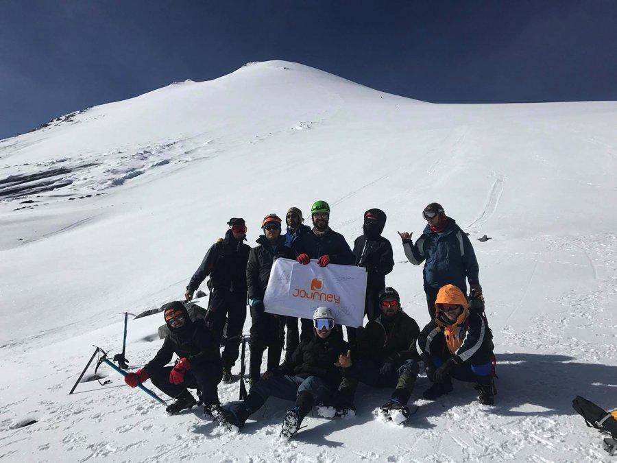 Montañistas sosteniendo bandera en Pico de Orizaba.