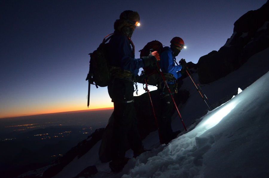 Dos montañistas ascendiendo con linternas al amanecer.